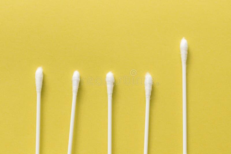 白色棉花芽或棉花棒在黄色背景 免版税库存图片