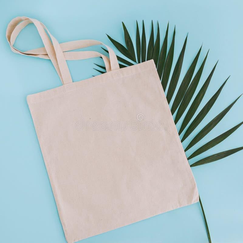 白色棉花袋子和棕榈叶在蓝色背景 假装为设计 免版税库存图片