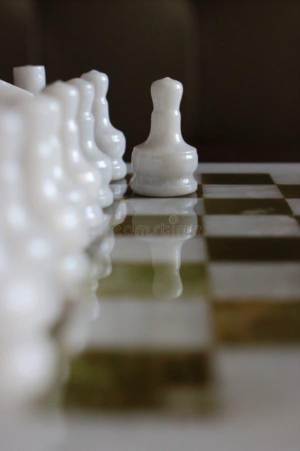 白色棋典当的第一运动在大理石棋枰的作为挑战和intelligant战斗概念 免版税库存图片