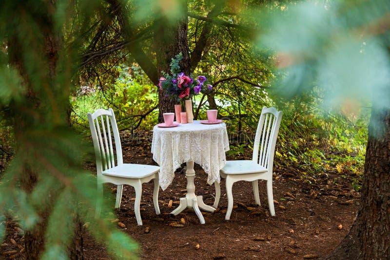 白色椅子、一张桌与桃红色杯子,一个蜡烛和花束 在街道上的欢乐照片区域有家具的,释放 库存图片