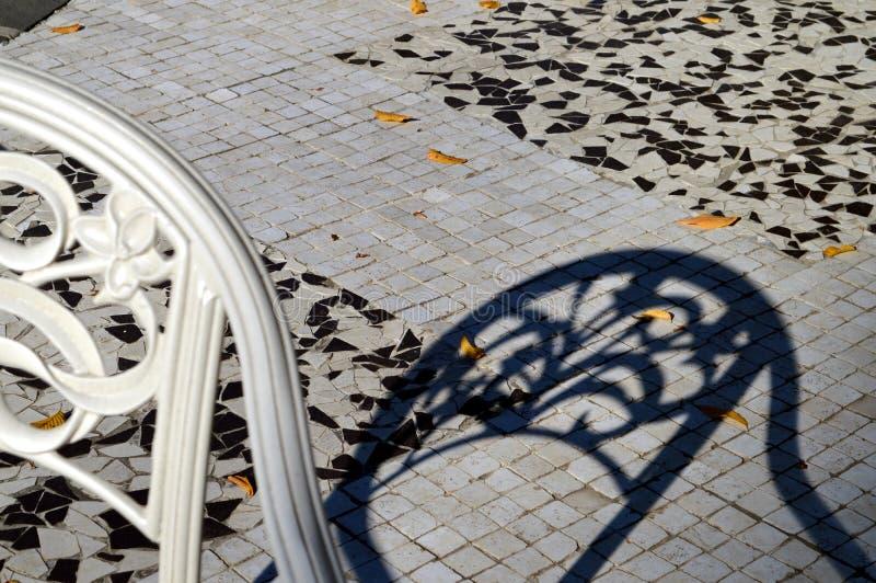 白色椅子和它的蓝色阴影在秋天 免版税库存图片