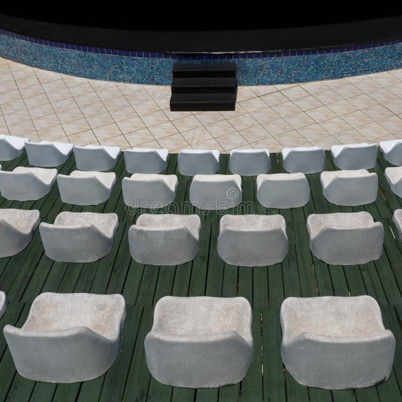 白色椅子行和一个阶段在一个室外观众席或大厅执行的介绍的 库存照片