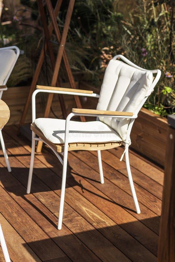 白色椅子,在一个木大阳台的现代设计 太阳、休息和孑然以你自己 库存图片