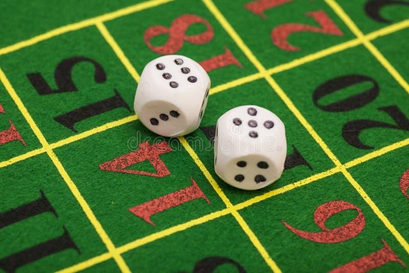 白色模子的卷在比赛表上的在赌博娱乐场 库存照片