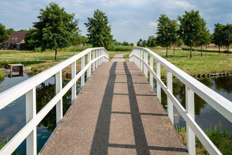 白色步行者和自行车桥梁在运河 库存照片