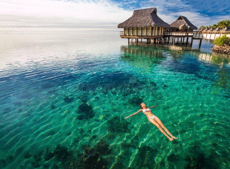 白色比基尼泳装游泳的妇女在珊瑚盐水湖, Moorea,塔希提岛 免版税库存图片