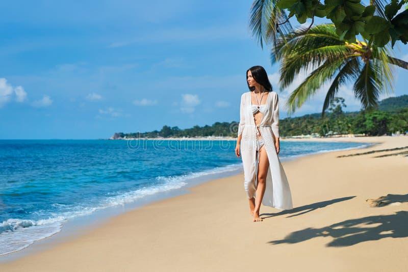 白色比基尼泳装的俏丽的年轻女人赤足走在热带海滩的海岸的 免版税库存图片