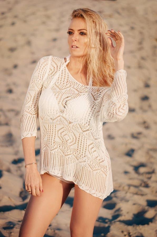 白色比基尼泳装的可爱的年轻白肤金发的妇女在白色沙子 秀丽,时尚,假期概念 库存图片