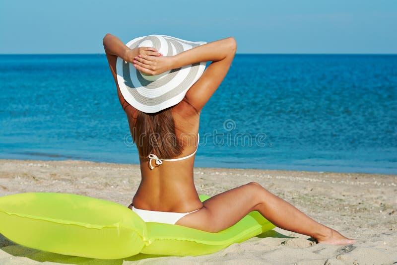 白色比基尼泳装的美丽的愉快的妇女有在海滩的黄色可膨胀的床垫的 免版税库存照片
