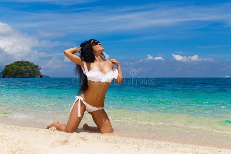 白色比基尼泳装的美丽的年轻浅黑肤色的男人在一个热带海滩 S 免版税库存照片