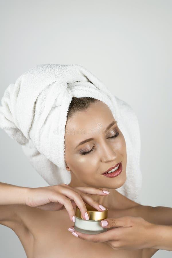 白色毛巾的可爱的白肤金发的妇女在她的顶头藏品和打开秀丽奶油在她的手上隔绝了白色 免版税库存图片