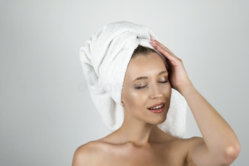 白色毛巾的美丽的年轻女人在她的在她的顶头关闭附近的头藏品手上被隔绝的白色背景 图库摄影
