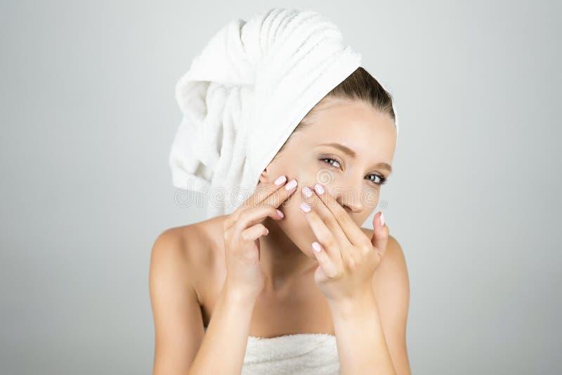 白色毛巾的美女在她的紧压在她的面颊被隔绝的白色背景的头丘疹 免版税图库摄影