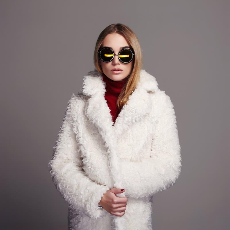 白色毛皮和太阳镜的美丽的冬天女孩 背景美丽的方式女孩查出的空白冬天 15个妇女年轻人 免版税库存照片