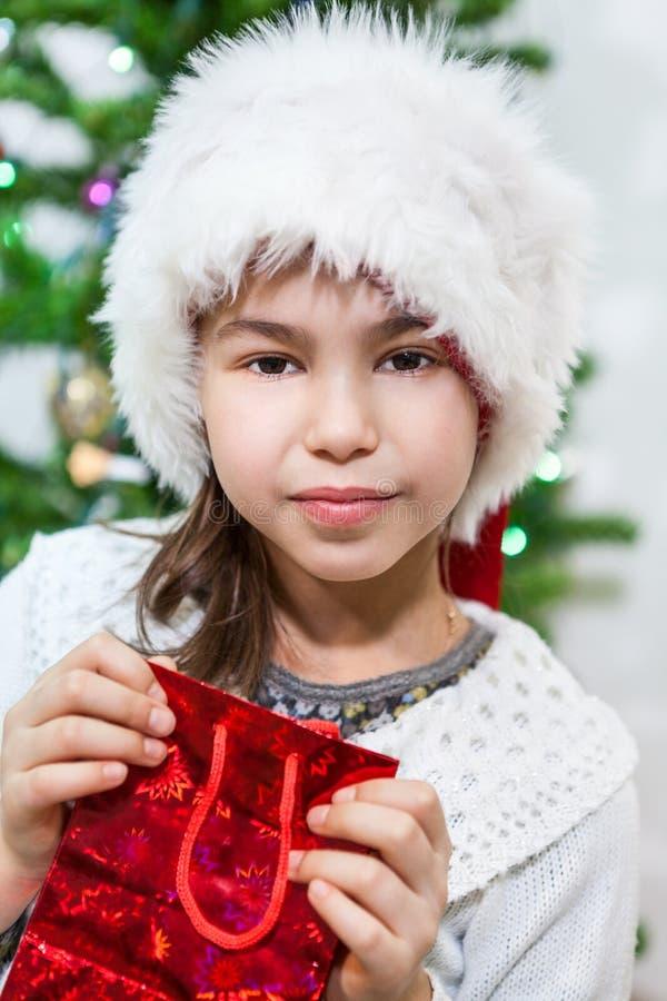白色毛皮圣诞老人帽子的小白种人女孩在手上的拿着红色礼物袋子 图库摄影