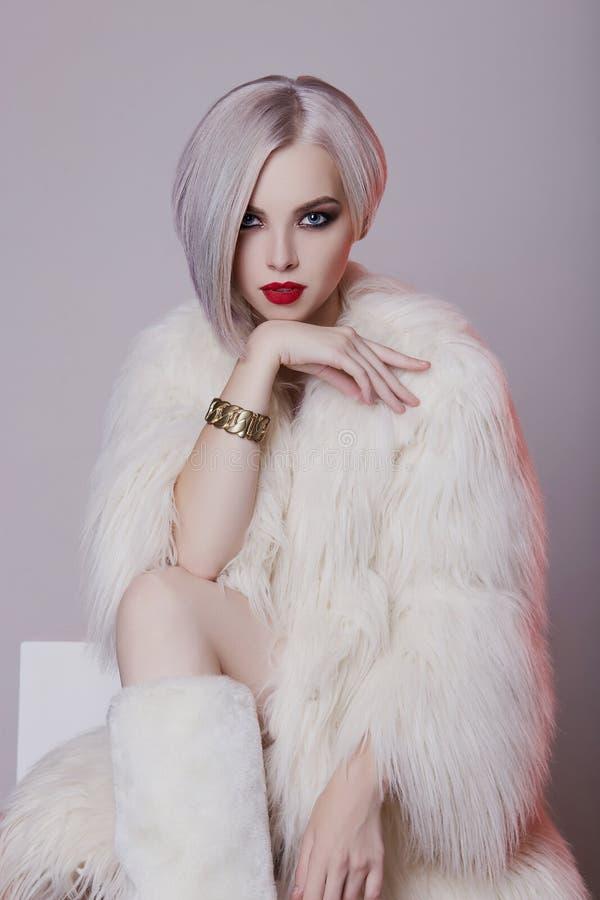 白色毛皮的美丽的白肤金发的妇女 免版税库存照片