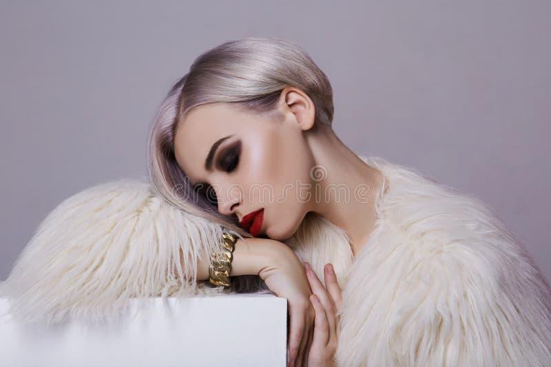 白色毛皮的美丽的白肤金发的少妇 免版税库存照片