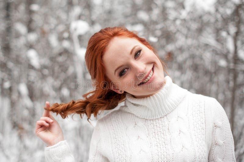 白色毛线衣的姜女孩在冬天森林雪12月在公园 背景圣诞节关闭红色时间 图库摄影