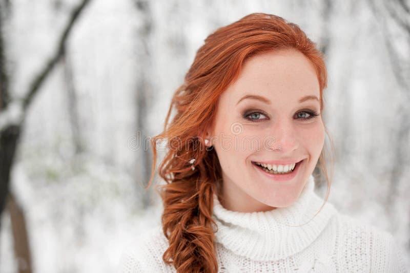 白色毛线衣的姜微笑的女孩在冬天森林雪12月在公园 画象 圣诞节逗人喜爱的时间 库存照片