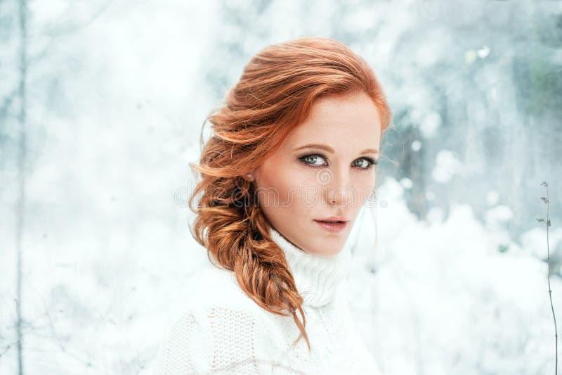 白色毛线衣的姜愉快的女性在冬天森林雪12月在公园 画象 圣诞节逗人喜爱的时间 免版税库存图片
