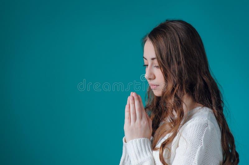 白色毛线衣的美丽的妇女折叠了她的在祷告的手对G 免版税图库摄影