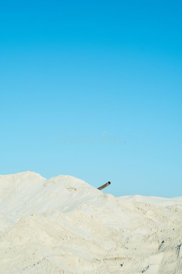 白色沙子、蓝天和生锈的管子 库存照片