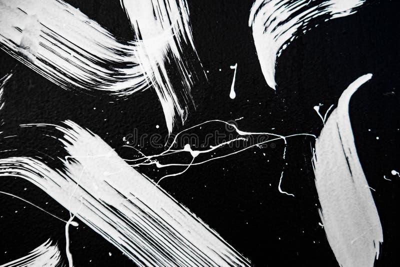 白色油漆,街道画,街道艺术纹理在黑墙壁上的 免版税库存照片