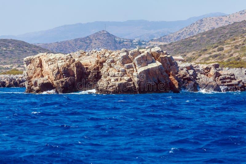 白色波浪和海峭壁-克利特典型的风景支持 库存图片