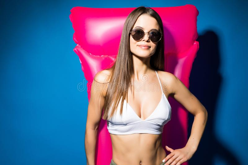 白色泳装和太阳镜的年轻美丽的微笑的妇女有桃红色可膨胀的床垫的,隔绝在蓝色背景 免版税图库摄影