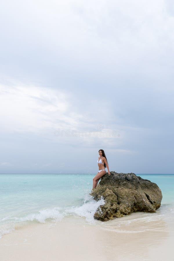 白色泳装的一少女坐在海滩的一块偏僻的石头 波浪击中了岩石 库存图片