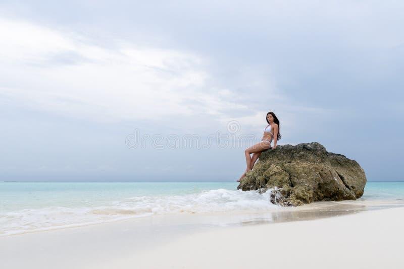 白色泳装的一少女坐在海滩的一块偏僻的石头 波浪击中了岩石 免版税库存图片