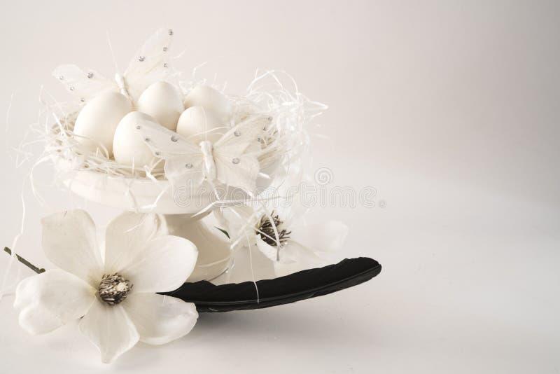 白色浪漫复活节场面,蛋糕立场用鸡蛋,花,反对白色背景,空间文本的 图库摄影