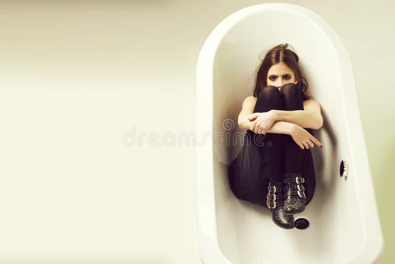 白色浴盆和美丽的少妇有黑嘴唇的 免版税库存图片