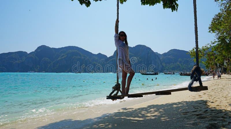 白色海角的美女和在摇摆的黑游泳衣 在海滩的摇摆 库存照片