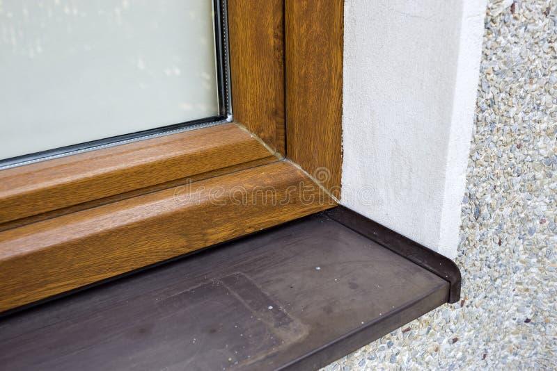 白色涂灰泥的房子墙壁特写镜头细节有最近安装的新的棕色塑料窗口和金属窗台的 现代 库存照片