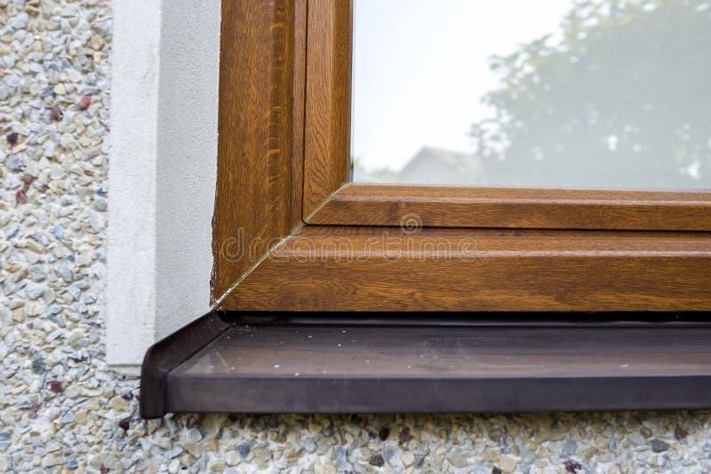 白色涂灰泥的房子墙壁特写镜头细节有最近安装的新的棕色塑料窗口和金属窗台的 现代 免版税图库摄影