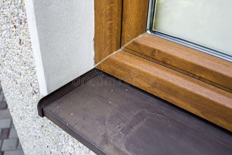 白色涂灰泥的房子墙壁特写镜头细节有最近安装的新的棕色塑料窗口和金属窗台的 现代 免版税库存图片