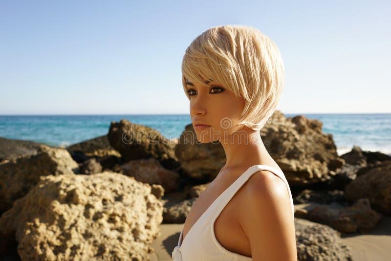 白色游泳衣的优美的妇女在海滩 免版税图库摄影