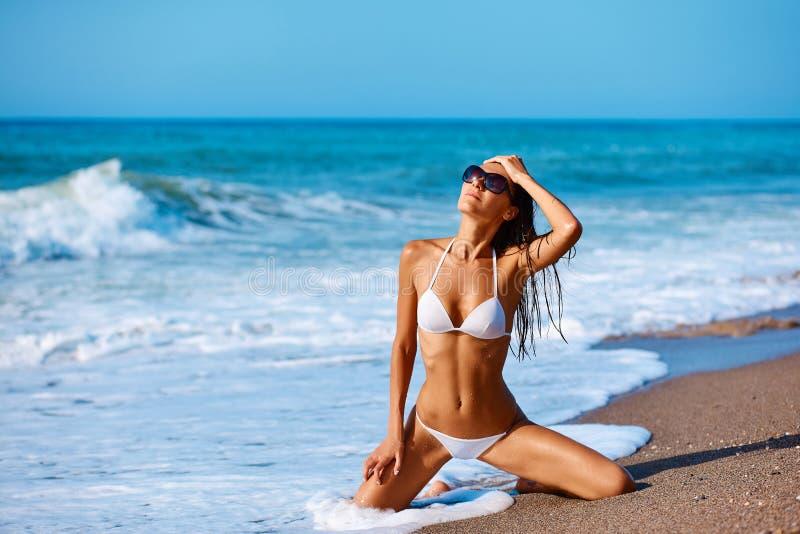 白色游泳衣的性感的美女和在沿海日落软的太阳光的创造性的帽子 免版税库存照片