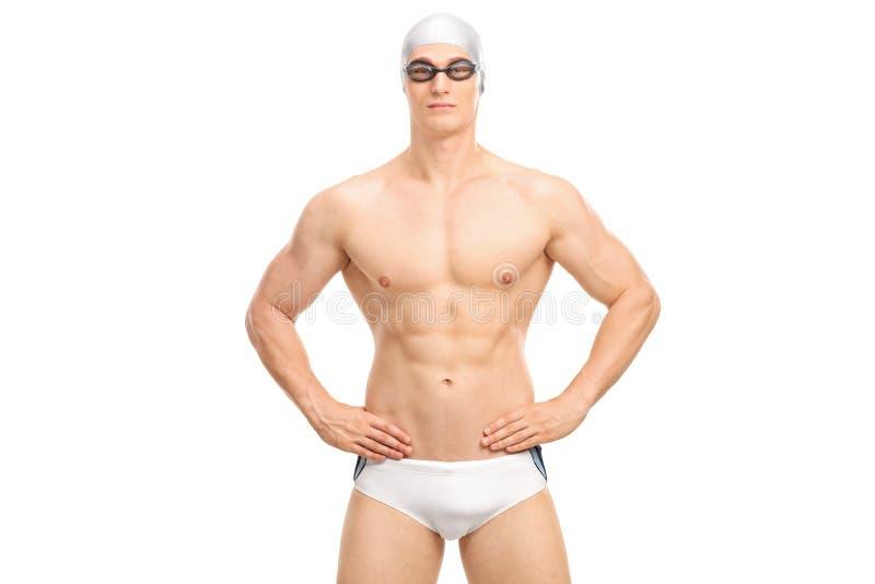 白色游泳裤的英俊的年轻游泳者 免版税库存图片