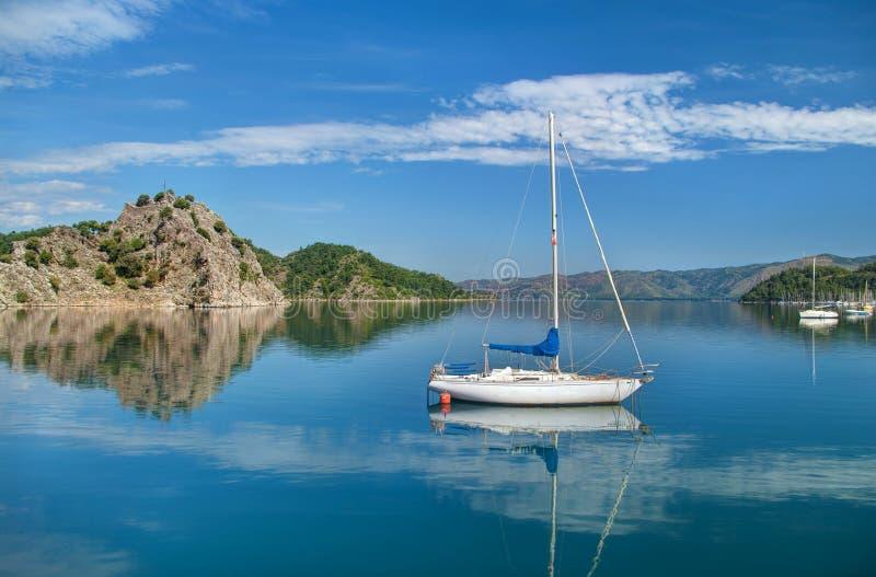 白色游艇在岩质岛附近的海有山和小ma的 图库摄影