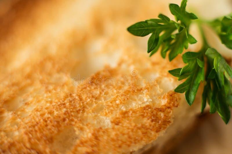 白色烤面包片特写镜头,宏观摄影,与荷兰芹小树枝  免版税库存图片