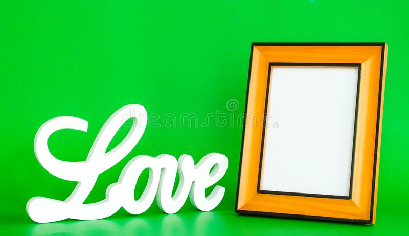 白色爱标志和空的画框在绿色背景 免版税库存照片