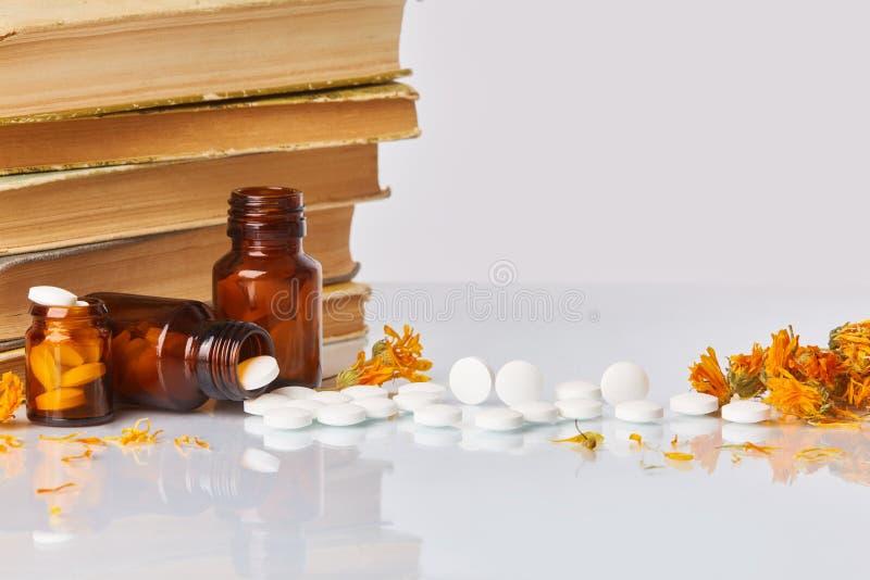 白色片剂和药片与万寿菊金盏草和旧书在白色镜子背景 免版税库存照片