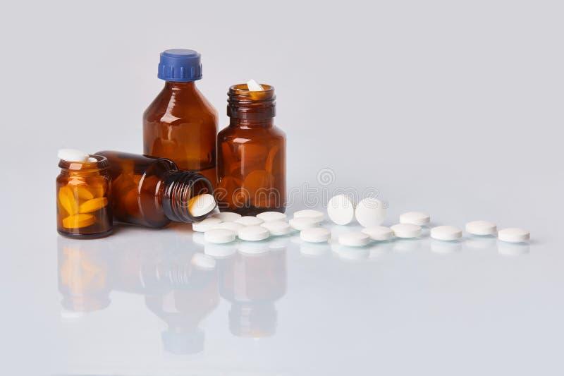 白色片剂和药片在墨镜瓶在白色背景 免版税库存图片