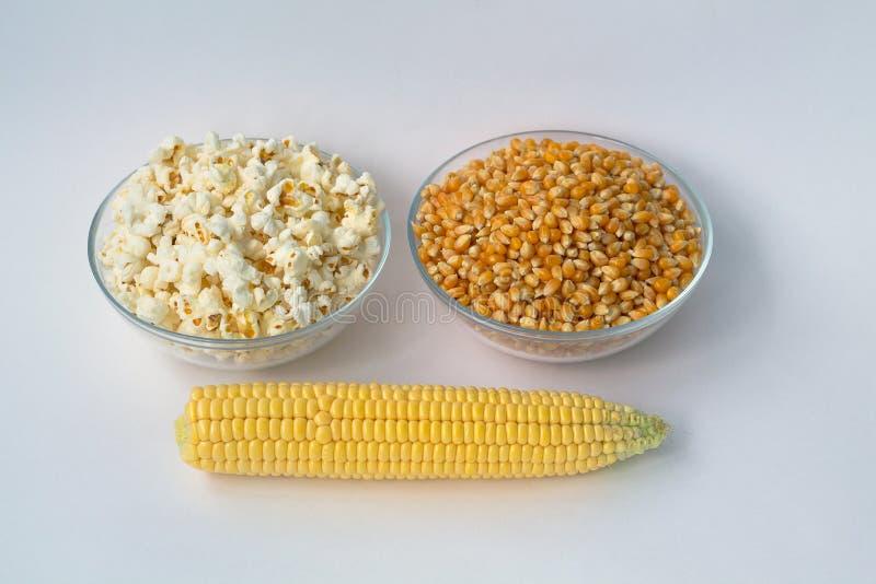 白色玉米花和黄色玉米在碗和玉米棒子在白色背景 免版税库存照片
