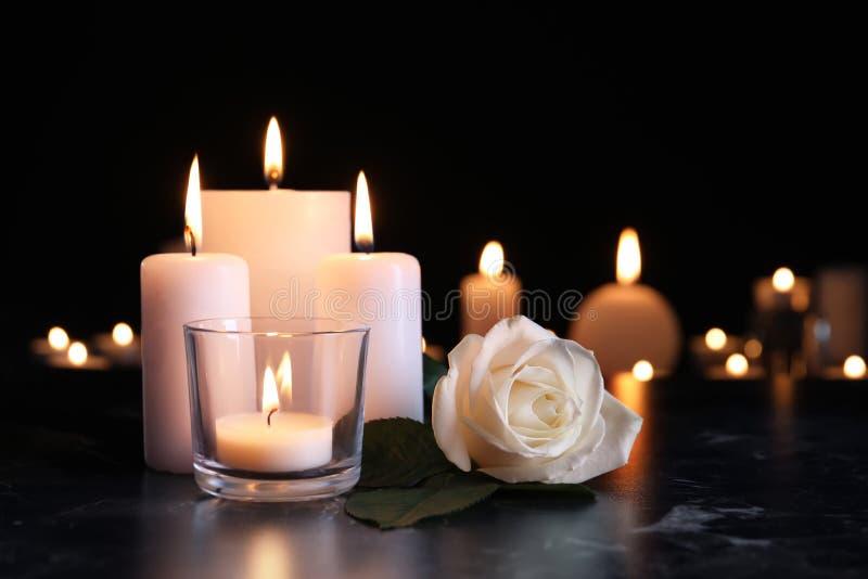 白色玫瑰和灼烧的蜡烛在桌上在黑暗中 免版税库存图片