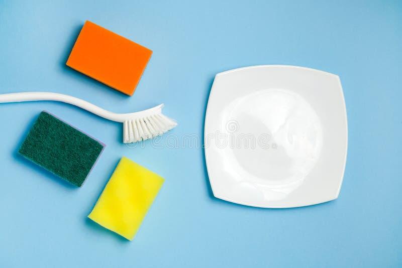 白色玻璃板、泡沫海绵和塑料刷子洗碗的 清洗的辅助部件 库存图片