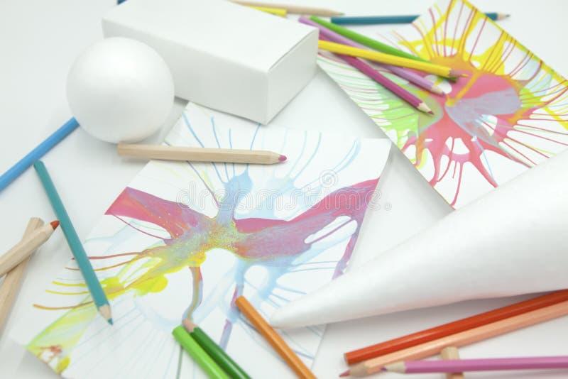 白色球形、棱镜和锥体与色的铅笔和抽象油漆在白色背景 免版税库存照片