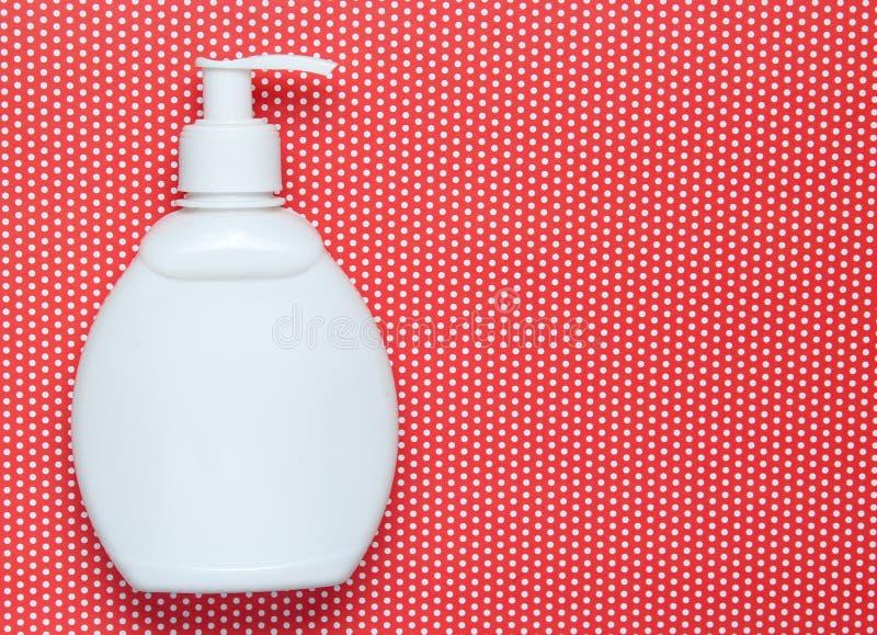 白色瓶在创造性的红色背景在圆点,顶视图的香波 库存照片
